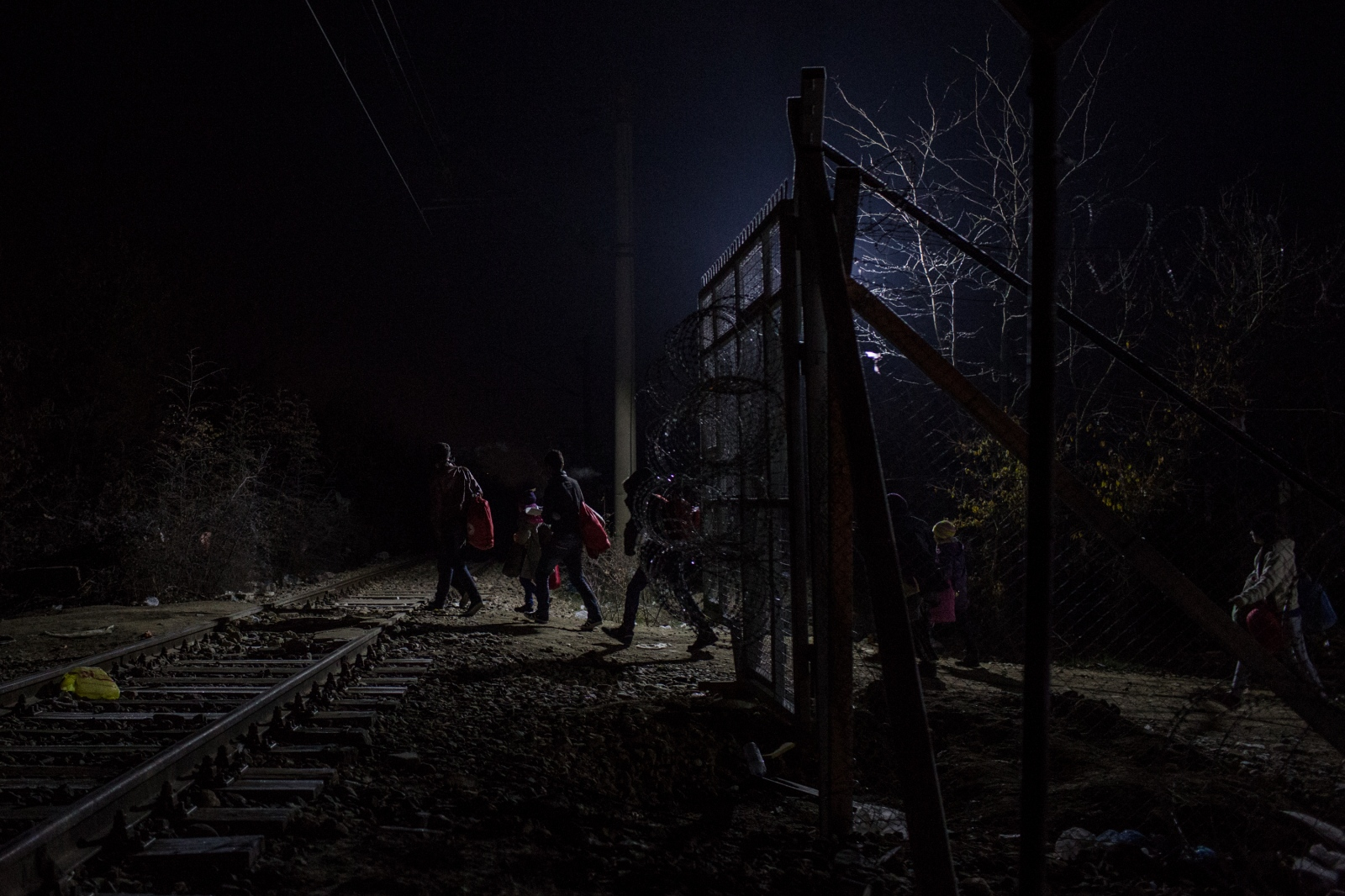 Refugees are seen walking on the railway tracks on the Macedonian side shortly after crossing the border between Greece and Macedonia on December 20, 2015.