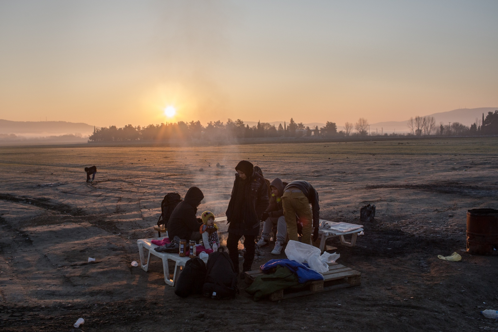 A refugee family warms themselves by a fire whilst waiting to cross the Greek-Macedonian border in Idomeni on December 20, 2015.