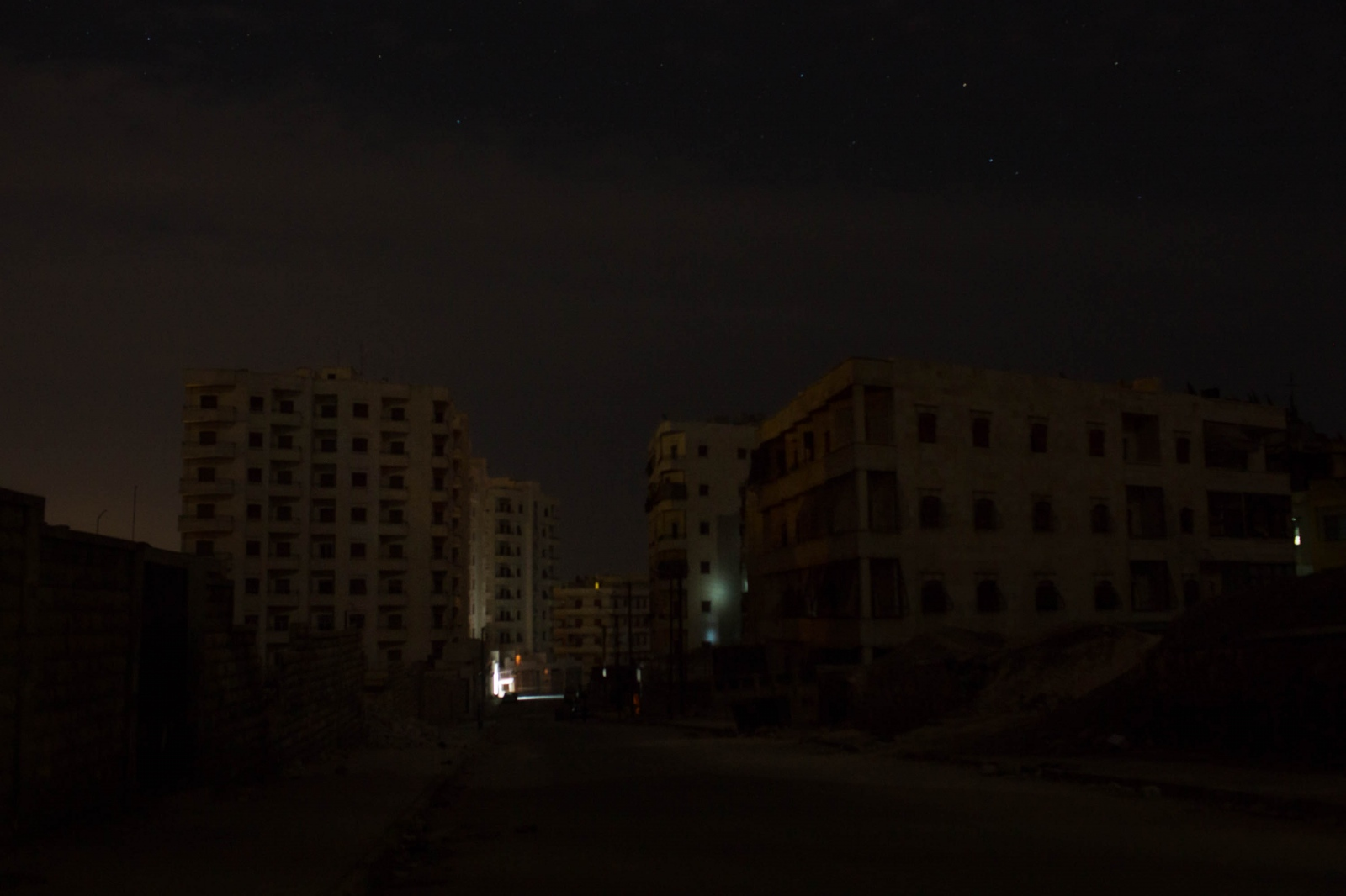 A view of apartment blocks without electricity in a neighborhood of Aleppo, Syria. 2013. The streets of Aleppo -- a city of approximately 3 million before the war -- seem desolate at night. Opposition-held areas change from mostly bustling middle class neighborhoods, to a series of empty boulevards and silent buildings. Look hard enough and the destruction of the city becomes apparent in the darkness. Climb high enough and the disparity between government and opposition-held neighborhoods become apparent: the government side is gleaming with lights from buildings and street lamps. A military hospital there, a government building there. A main square there. The opposition side has paid dearly for their revolt: death, destruction, and rarely any electricity. Only recently have the lights come back on in some neighborhoods where the locals were able to patch their own electricity together. The aim of these photos was to convey the accessible parts of the city when night fell. Electricity had been out to most of the opposition areas wedged in an uneasy patchwork between government and rebel neighborhoods for nearly seven months by the time these photos were taken. The indiscriminate shelling from the ground and sky, the invisible snipers--the physical war-- along with the psychological war or this conflict have caused immeasurable damage and has exacted a heavy toll on one of Syria's most important, historic cities and its population. Between 13-15,000 people are estimated to have died in Aleppo (civilians and combatants combined) and countless homes and shops have been lost. Yet the city still endures, often quietly.