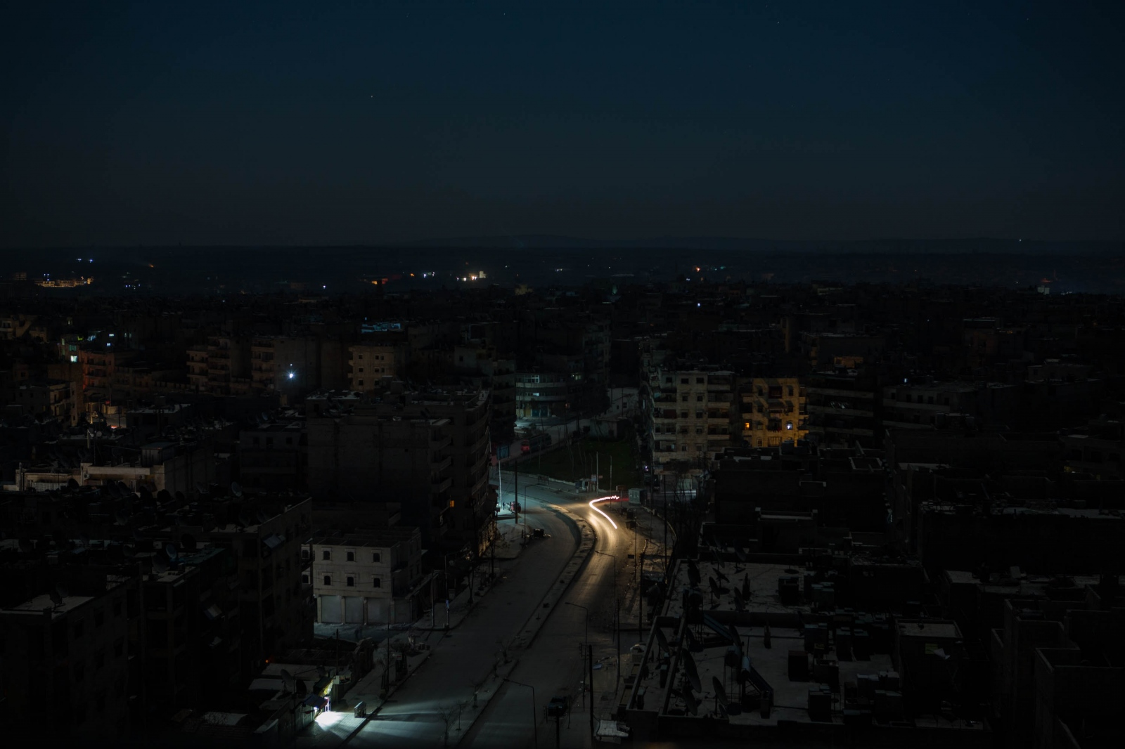 A street is briefly lit by car headlights near the Al Sukkari neighborhood of Aleppo, Syria. 2013.
