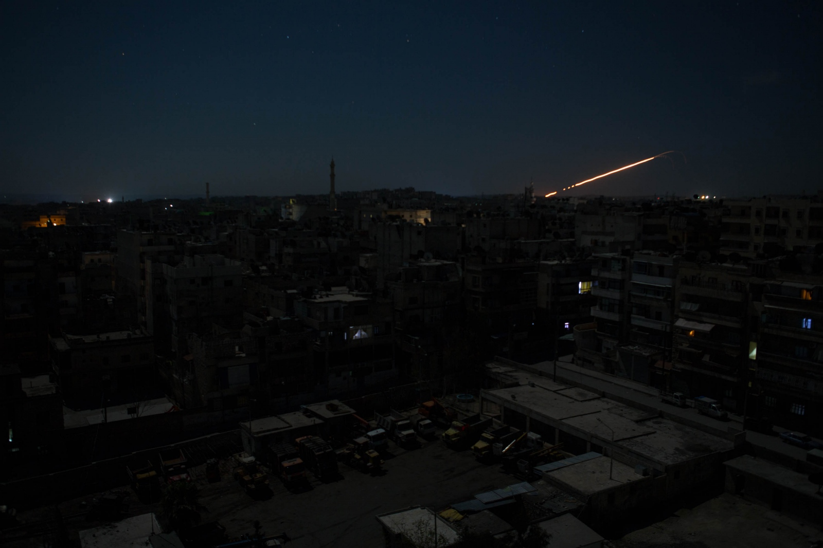A trail of light follows a rocket launch from a government held area of Aleppo, Syria. 2013.