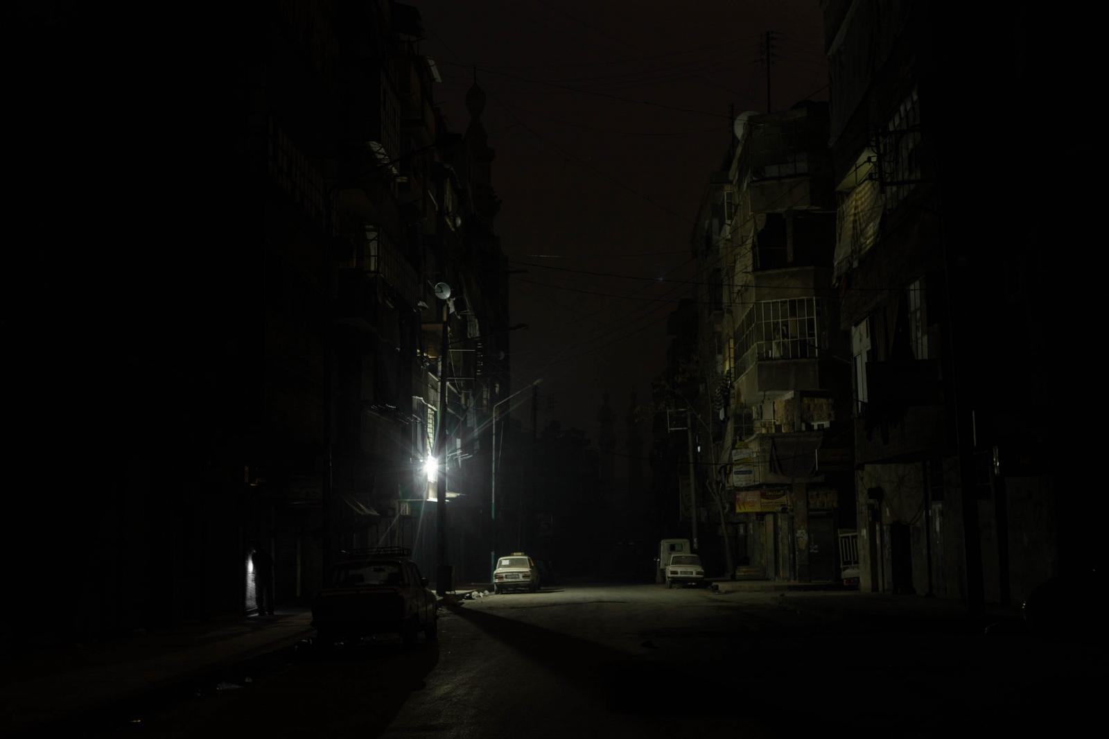 A light, running off a generator, brightens a street near the frontline of Salaheddin neighborhood of Aleppo, Syria. 2013.