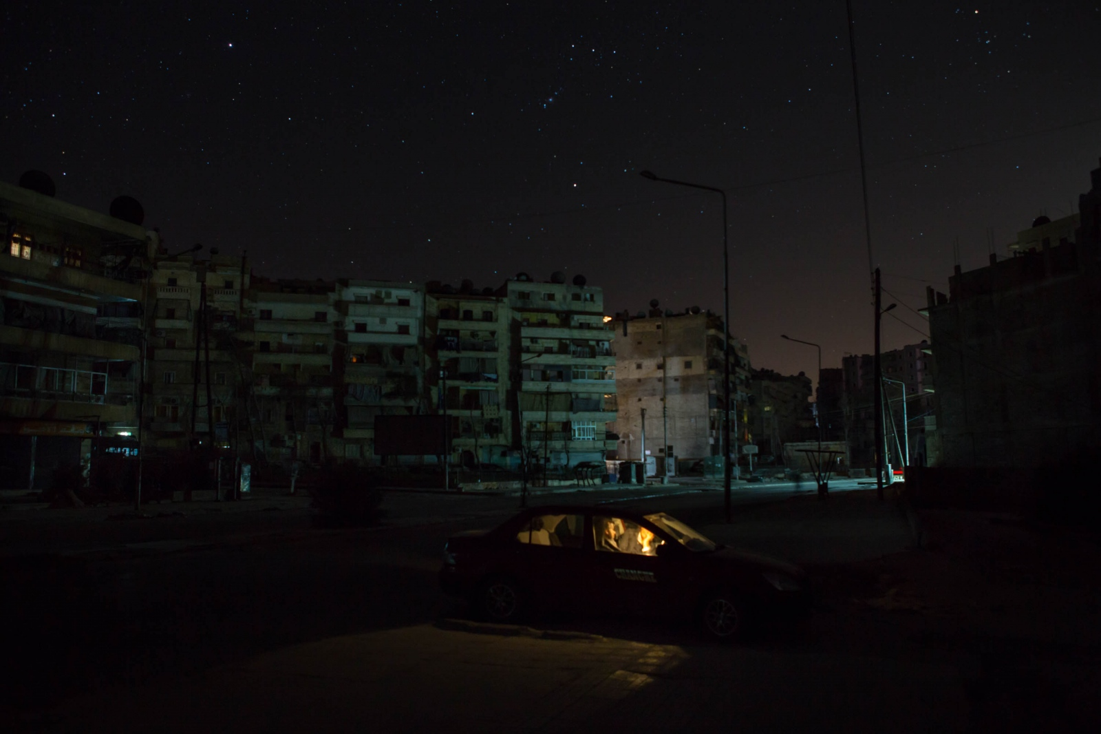 Two people are lit by the interior car light in a residential neighborhood of Aleppo, Syria. 2013.
