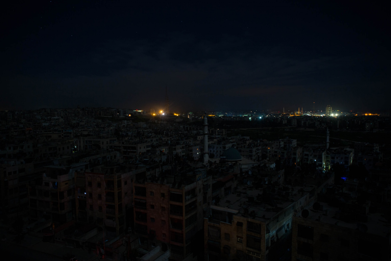 Opposition-held Aleppo, foreground, is seen against a brightly lit government held area in the horizon. Aleppo, Syria. 2013.