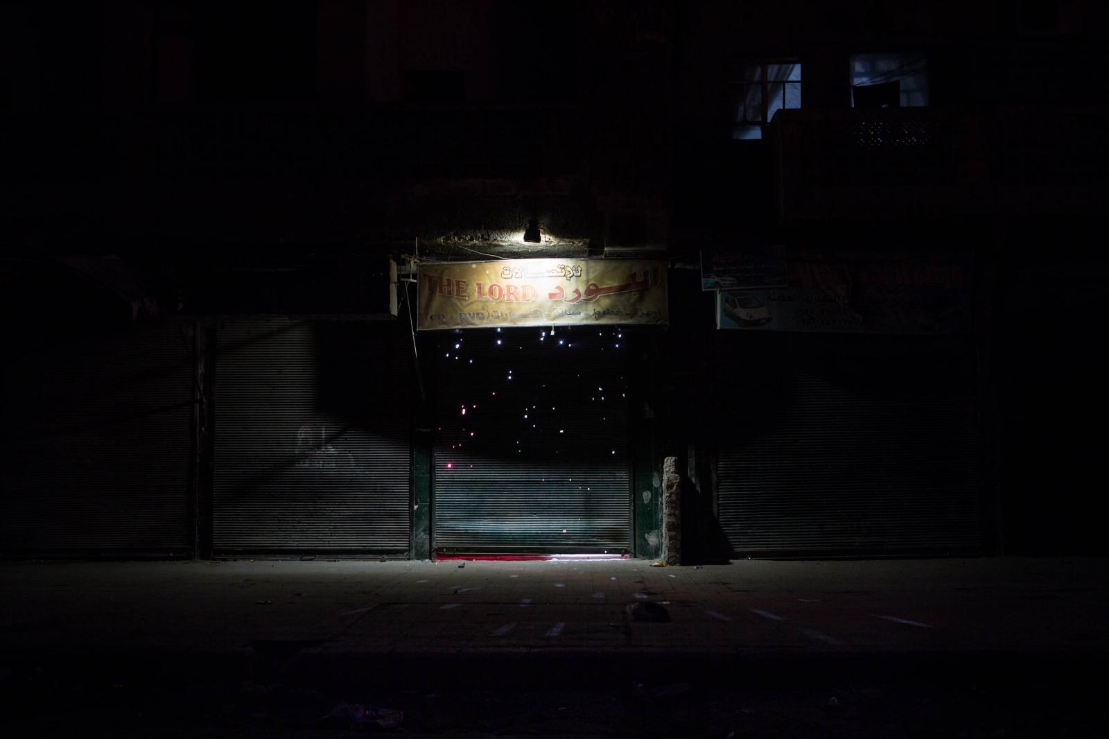 Rays of light shine through a shrapnel ridden metal gate enclosing a store, Aleppo, Syria. 2013.