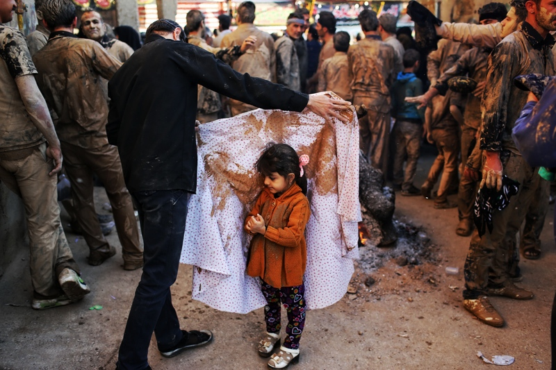 People of Khorramabad city smear themselves with mud and after drying beside a fire start mourning for Imam Hossein (AS). During this ceremony, children also mourn beside their parents. A man is drying the chador (hijab) of his 4-year-old child before the mourning starts. (Lorestan / khorram abad)