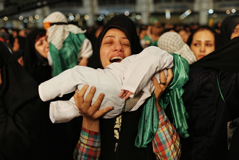 """Hosseini Infants"" is a mourning ceremony held for Ali Asqar, the 6-month-old son of Imam Hossein (AS) who was martyred by Yazid forces. During the ceremony, mothers mourn with their infants for Ali Asqar. A woman prays for Imam Hossein (AS) to heal her crippled child. (Tehran)"