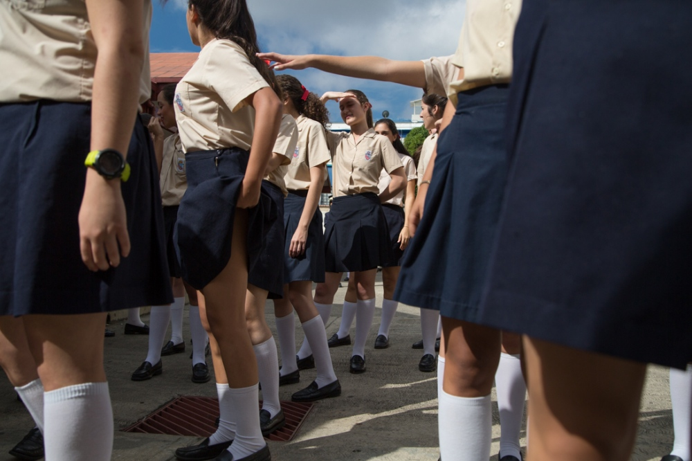 The girls during a military school practice. Even if they study in a private school they have to accomplish some educational requirements imposed by the Venezuelan Ministry of Education. The girls are together from the early morning until the end of the day. Colegio Cristo Rey de Altamira, Caracas. November, 22nd, 2017.