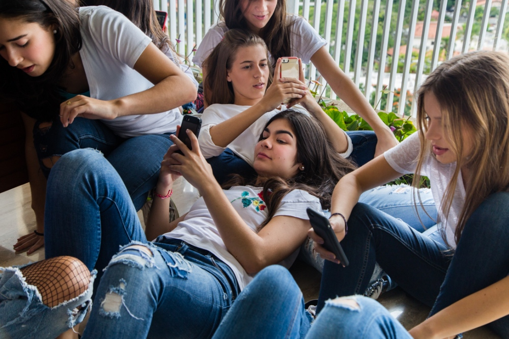 Girls checking their cell phones during a photo shooting brake. Pictures are for their instagram account. Altamira, Caracas. September, 30th, 2017.