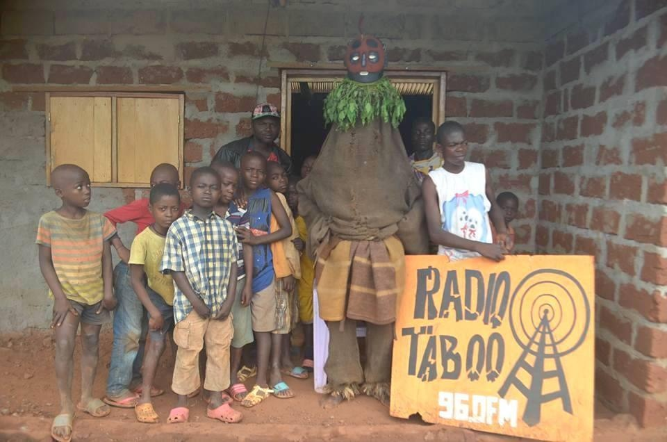 Meliti, one of the Tikar's gods pausing with children at the Radio Taboo station in N'ditam.