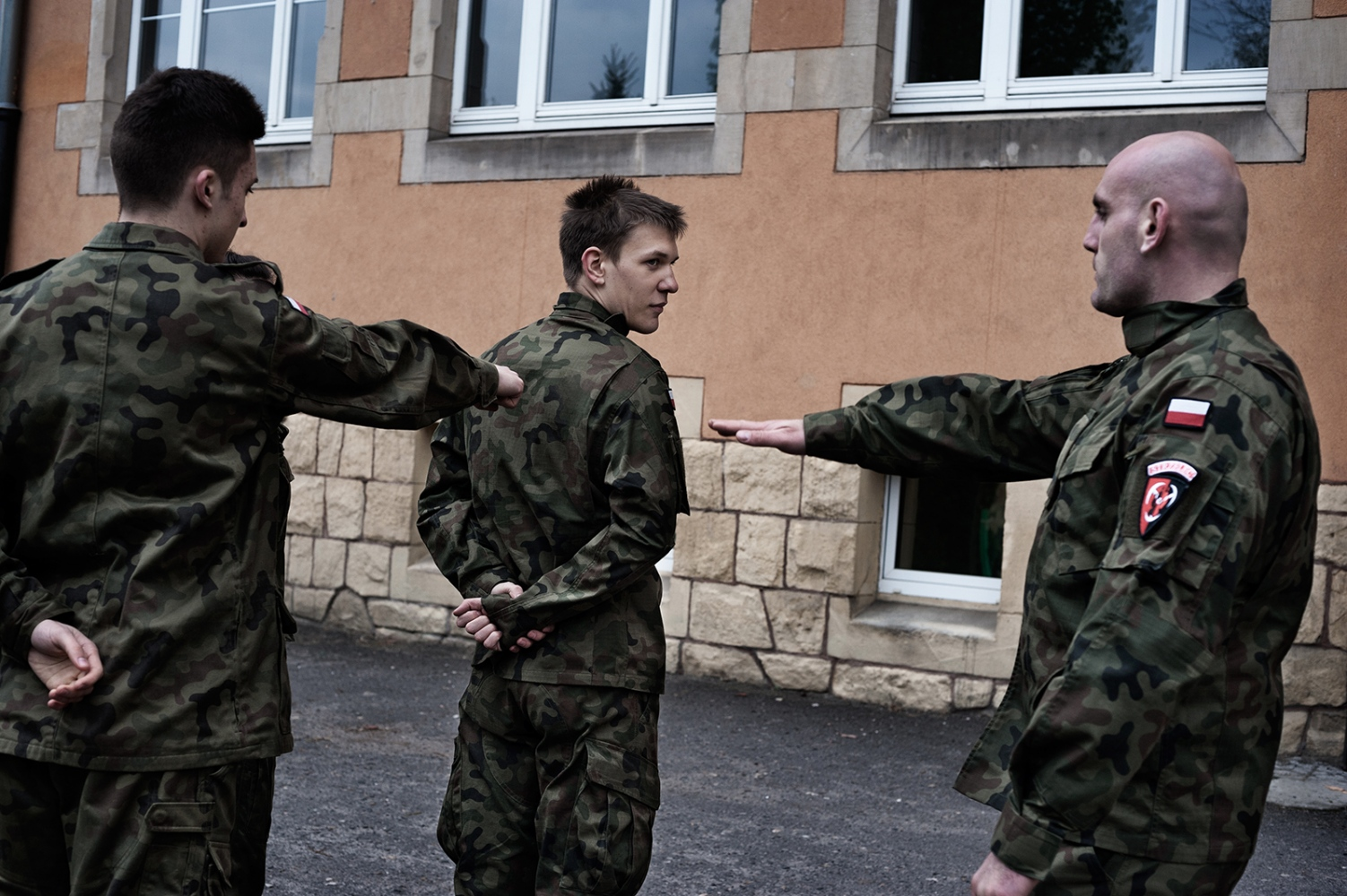 """Students from the public High School in Brzeg during the military training under the supervision of Sebastian Lipinski, the instructor in charge of the Unit 3060. Brzeg 2017 """"The discipline and military training are very important. The values we want to convey are summarized in three words: God, Honor and Fatherland. We promote integrity by taking the extinct Unbreakable Soldiers as an example. Each student chooses his referent, learns his biography and puts his nickname of war on the uniform."""" (Sebastian Lipinski) The Unbreakable Soldiers (also called Damned) were members of the National Army, the armed wing of the Polish secret State during the Second World War. Persecuted by the communist regime, today they are elevated to the rank of national heroes. However, some were directly involved in murders of Polish civilians of Belarusian origin – crimes that took place in northeastern Poland 70 years ago. Many Poles avoid talking about these issues, while current governmental instances minimize the magnitude of those events or question the veracity of some testimonies."""