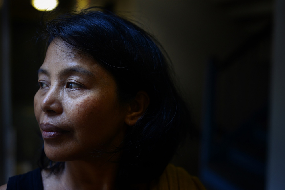 Portrait of Edith Mendoza, 51, in the hallway of her apartment building in Queens, NY. Filipina nanny Edith Mendoza moved to the U.S. to care for a German diplomat's family. She ended up working 100-hour weeks for $4 an hour and becoming seriously ill. She made it out in 2016.
