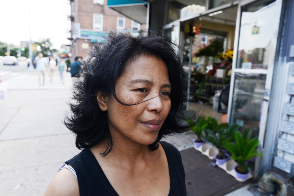 "Edith Mendoza, 51, in Queens, NY. ""When I got this job I felt blessed and filled with hope for my family. They paid regularly until four or five months everything changed. They demanded more work. I [asked] would they add more to my salary. They told me, 'Edith, everything is free for you.' Yes [they broke my contract], but I don't know everything at that time. I don't know about the [Domestic Workers' Bill of Rights]. I don't know what I am supposed to do, who to contact, so I just keep silent doing what they told me to do. I was powerless. I was scared I might lose my job or they might send me back to the Philippines."""