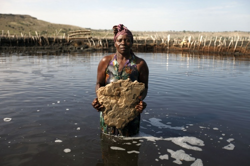 A salt worker holds a huge slab of salt she pulled out of Lake Katwe in Western Uganda. The lake sits in an extinct volcano and the salt forms at the bottom of the lake where it must be broken in to manageable sized pieces and brought to the surface. Full of pollutants and blistering heat makes working in the lake very hard.  Katwe, Uganda