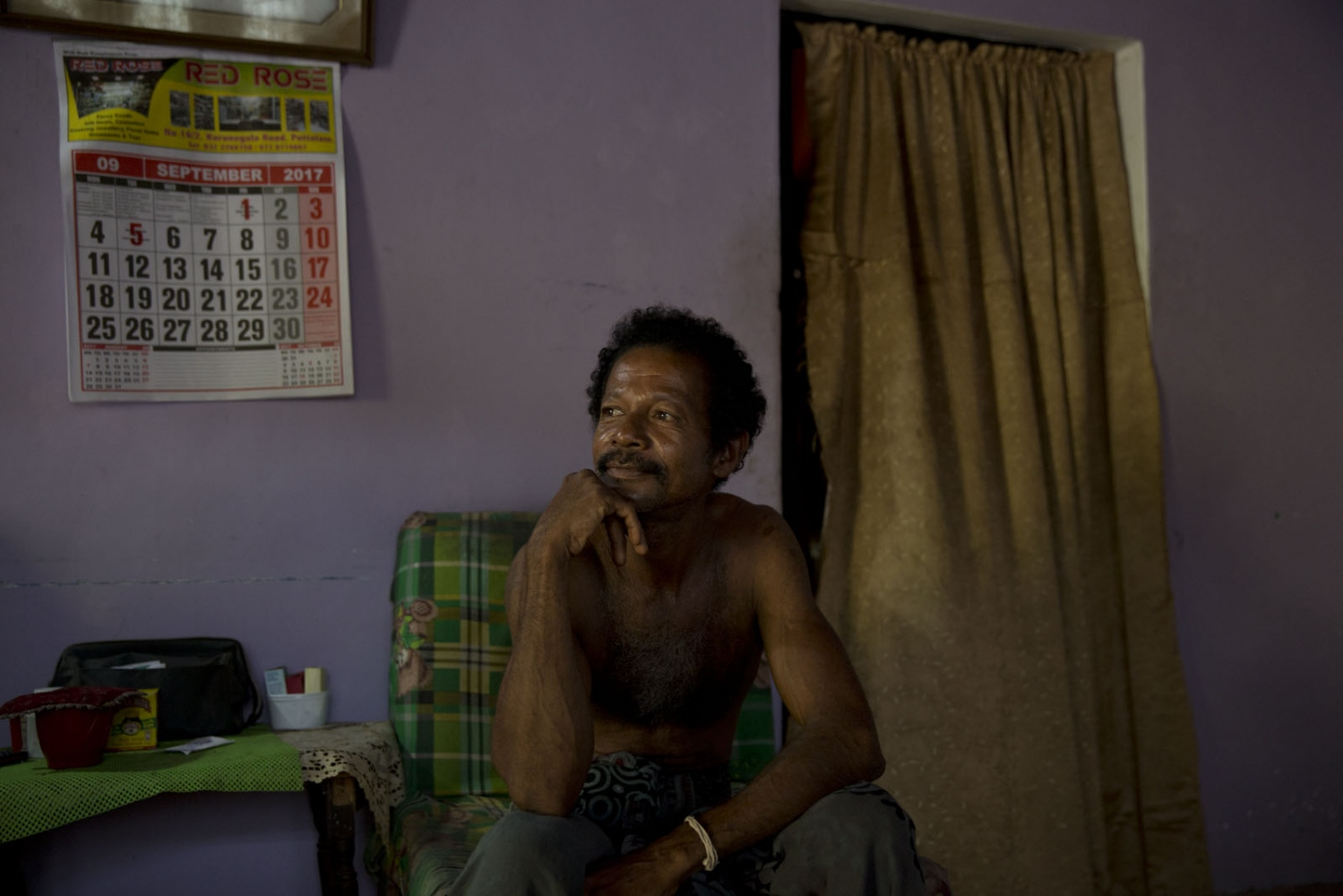 Johnson, an Afro-Sri Lankan, sits in the front room of his house in the Good Shed area of Puttalam town.  Sri Lanka