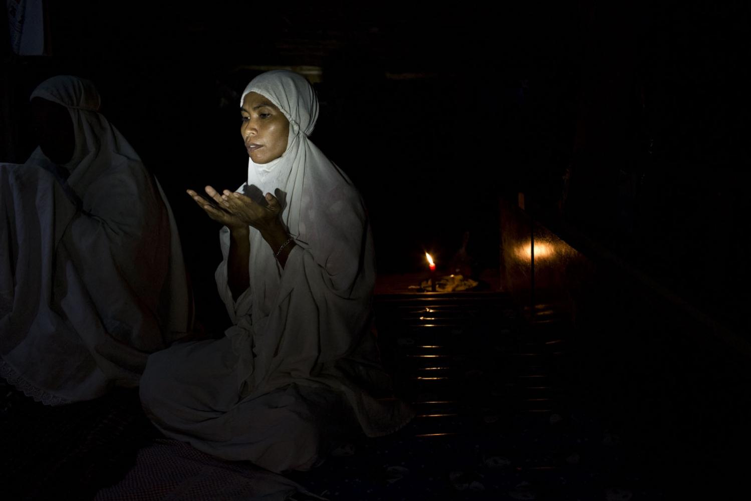 Janya Ruangthong, 36, originally from neighbouring Krabi province prays in her house. Her family is one of five Muslim familes living in Klong Sai Pattana.  Surat Thani, Thailand