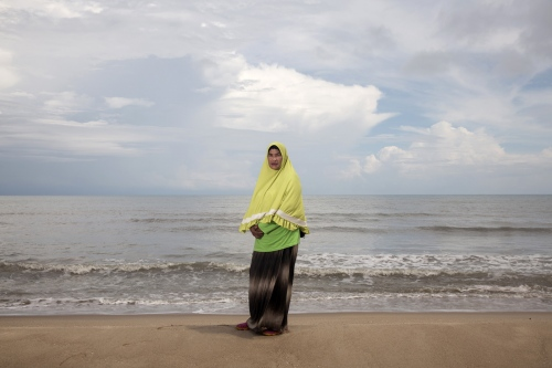 Rokeeyoh Sana-Ae stands on the beach located next to her community in the Tae Pa District of Songklah Province. Where she stands is the proposed site for a coal-powered power plant which the community vigorously opposes saying it will destroy the natural habitat of the area and their community.  Songklah, Thailand