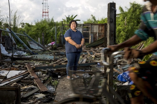Nutchanart Thanthong stands in the remains of a destroyed house in the small slum community fighting forced evictions. For over 20 years she has assisted communities in and around Bangkok who are facing eviction.  Samut Prakan, Thailand