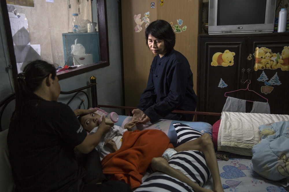 Preeyanan Lorsermvattana sits in the bedroom of a mother and son whom she assisted in receiving compensation after a hospital doctor injected the pregnant mother with a drug that led to the child being born severely mentally and physically disabled. Now 9 years old she continues to help the family.  Bangkok, Thailand
