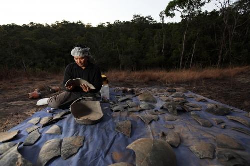Tep Sockha, a Cambodian ceramic expert, reconstructs a damaged jar found in the Cardamon Forest probably broken by falling rocks.  Koh Kong, Cambodia