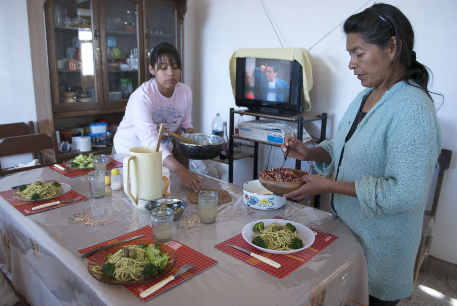 "Irene and her daughter prepare dinner with pesto and broccoli harvested from their garden. She said, ""Now we feel happy. We have a place to live, to be calm and to be at peace. If my daughters want to bring their friends over, they can do that without problems. We couldn't do that before."" Sivingani, Cochabamba, Bolivia, 2014."