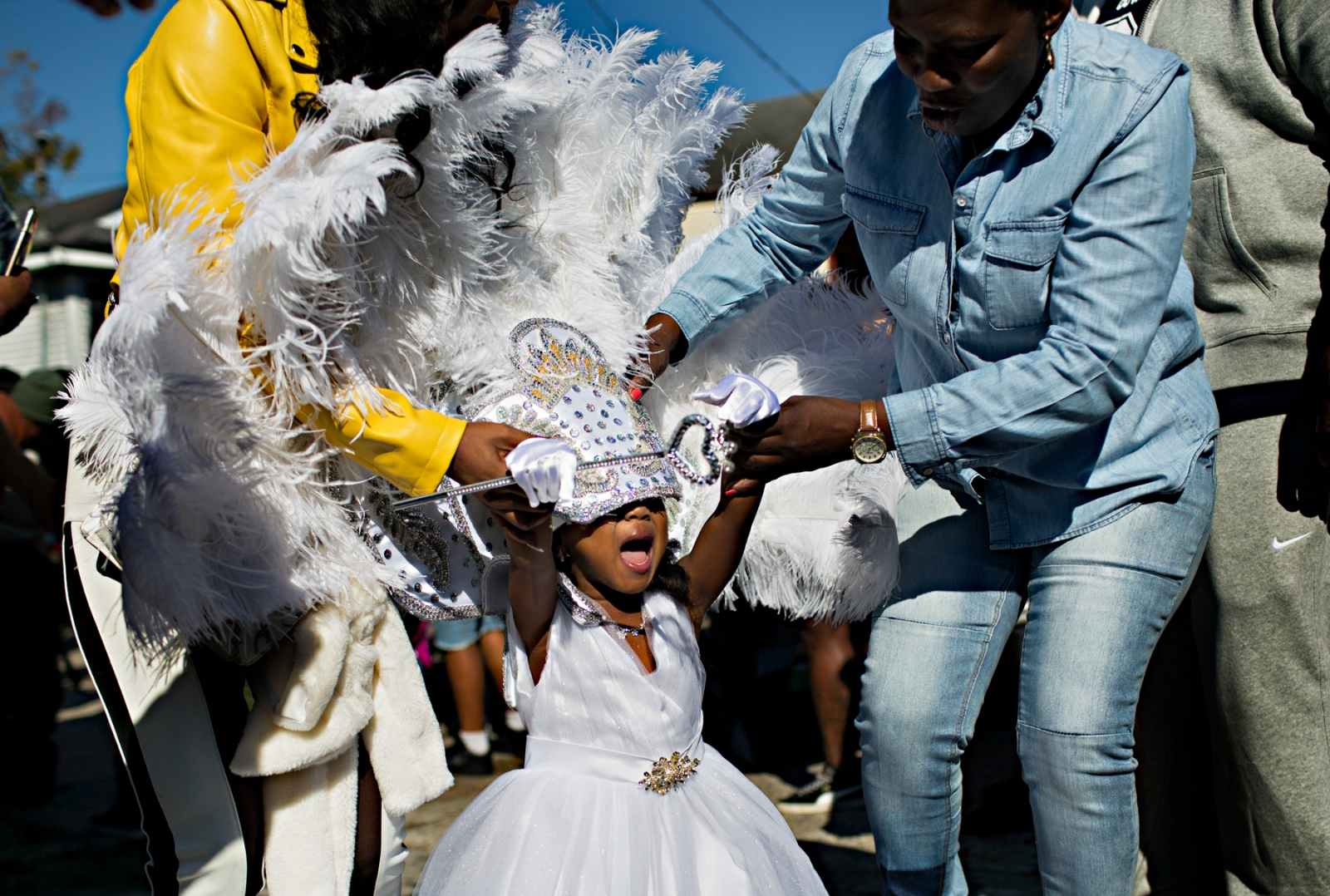 Duchess Blair Smith has some trouble with her feather headdress on her way to the float on which she is to ride during the Second Line Parade.