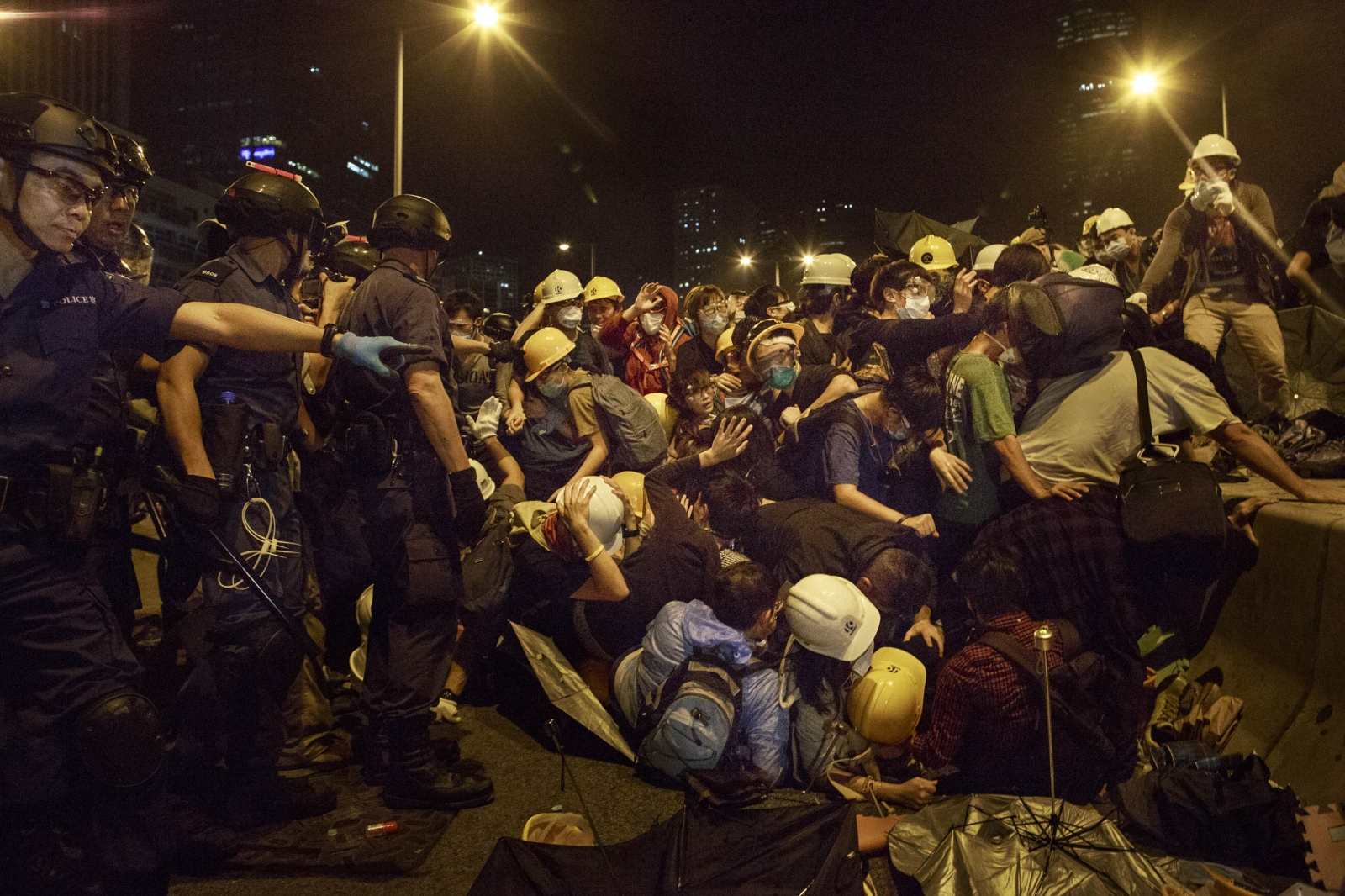Protestors attempt to cross a barricade during a violent night of scuffles with the police in the Admiralty district of Hong Kong, in the early hours of December 1, 2014. Protestors attempted to retake and occupy a major road that had earlier been cleared by the police weeks earlier. Pro-democracy demonstrators blocked major thoroughfares and roads of the city for just over two months, calling for universal suffrage in 2017 with the right to elect the city's own chief executive-- without Beijing's pre-approval of candidates-- a demand that remains rejected by Beijing.