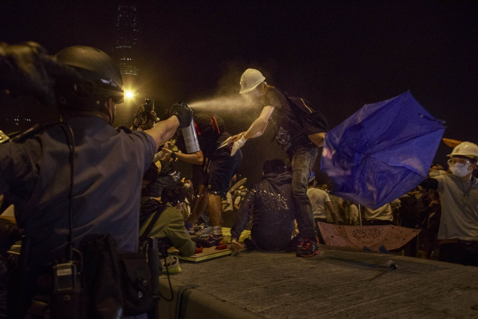 A protestor is sprayed with pepper spray during a violent night of scuffles with the police in the Admiralty district of Hong Kong, in the early hours of December 1, 2014. Protestors attempted to retake and occupy a major road that had earlier been cleared by the police weeks earlier.