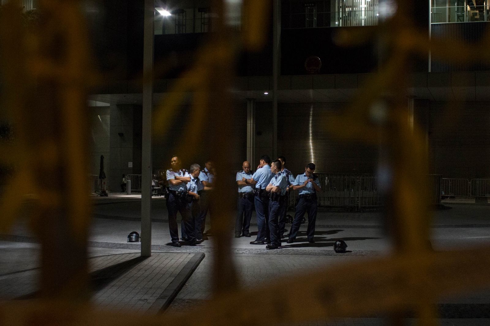 Policemen, gathered in a courtyard of the Legislative Council Offices, are seen through yellow ribbons tied to the gate by pro-democracy protestors on October 6, 2014, in Admiralty, Hong Kong.