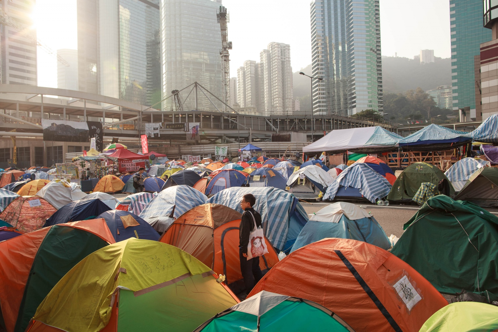 A pro-democracy protestor stands amidst a sea of tents on Harcourt Road, a major thoroughfare, over a month in to protests calling for universal suffrage in 2017 with the right to elect the city's own chief executive-- without Beijing's pre-approval of candidates-- a demand that remains rejected by Beijing.