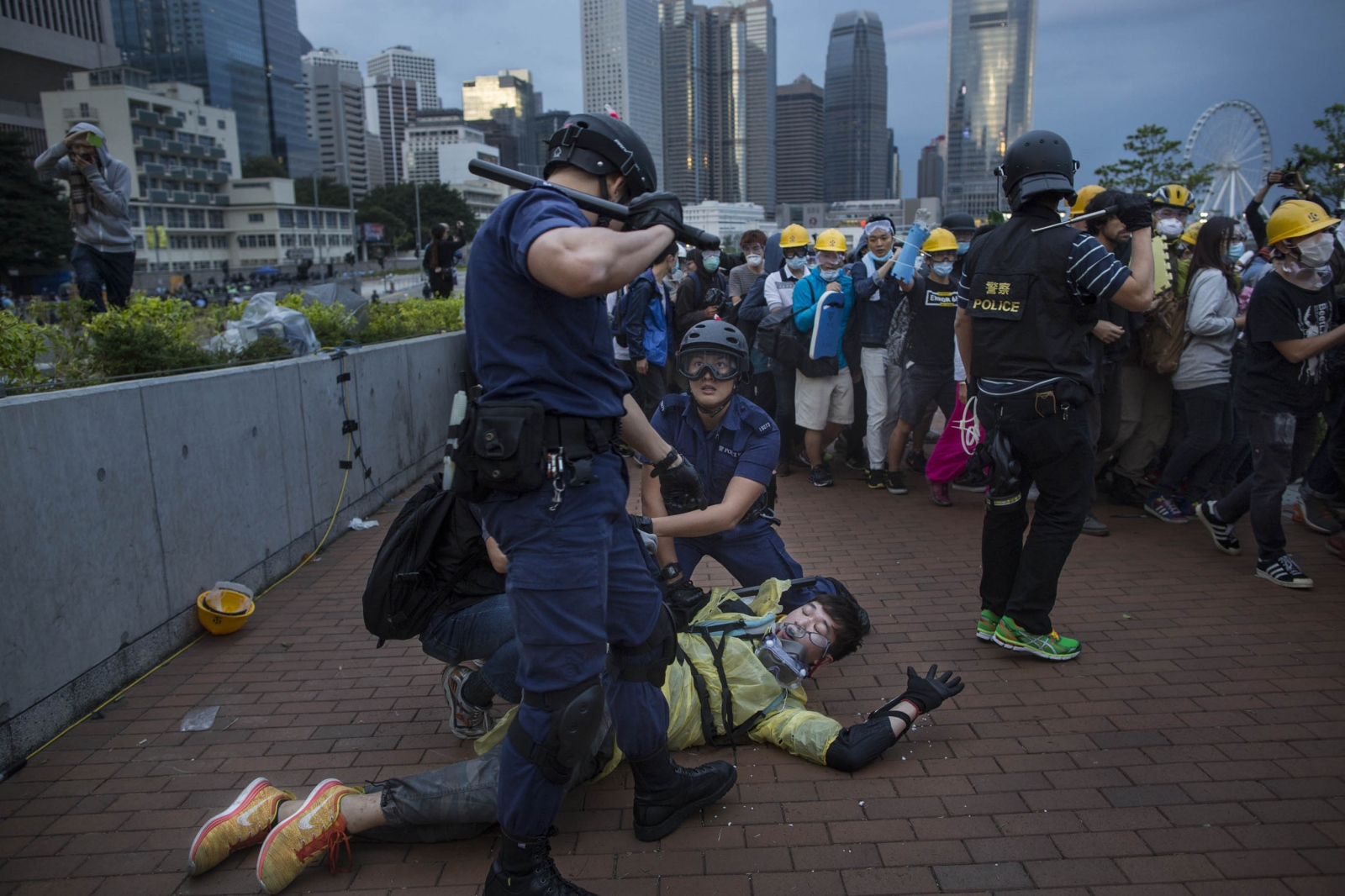 A protester is accosted by the police after being beaten with a baton following a violent night of scuffles with the police in the Admiralty district of Hong Kong, in the early hours of December 1, 2014. Protestors attempted to retake and occupy a major road that had earlier been cleared by the police weeks earlier.