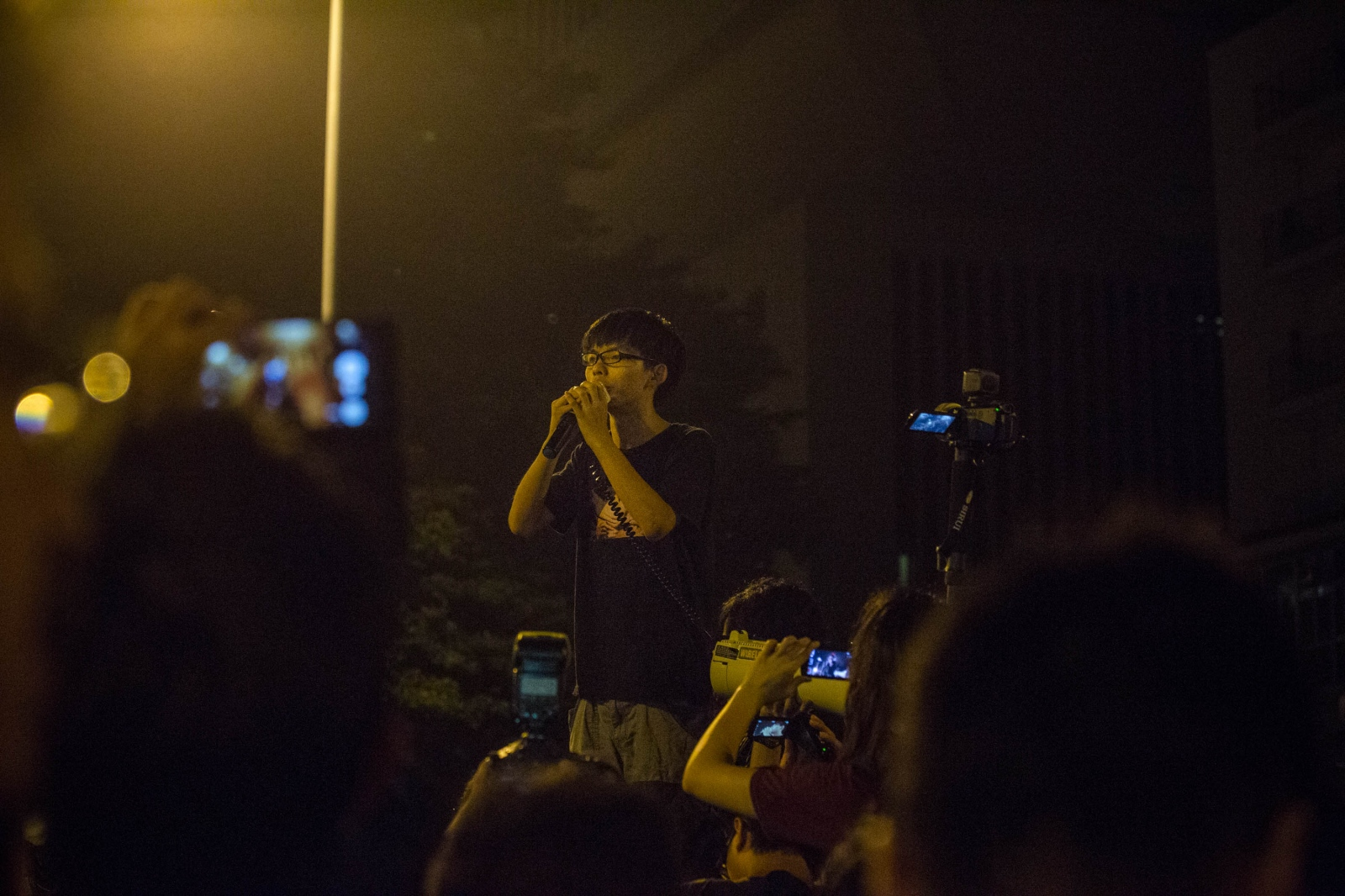 17-year-old activist Joshua Wong, founder of the group Scholarism and credited with starting the campaign of civil disobedience to advocate for universal suffrage in Hong Kong, speaks to protestors during a tense night outside the Chief Executive's office in the early hours of October 3, 2014.