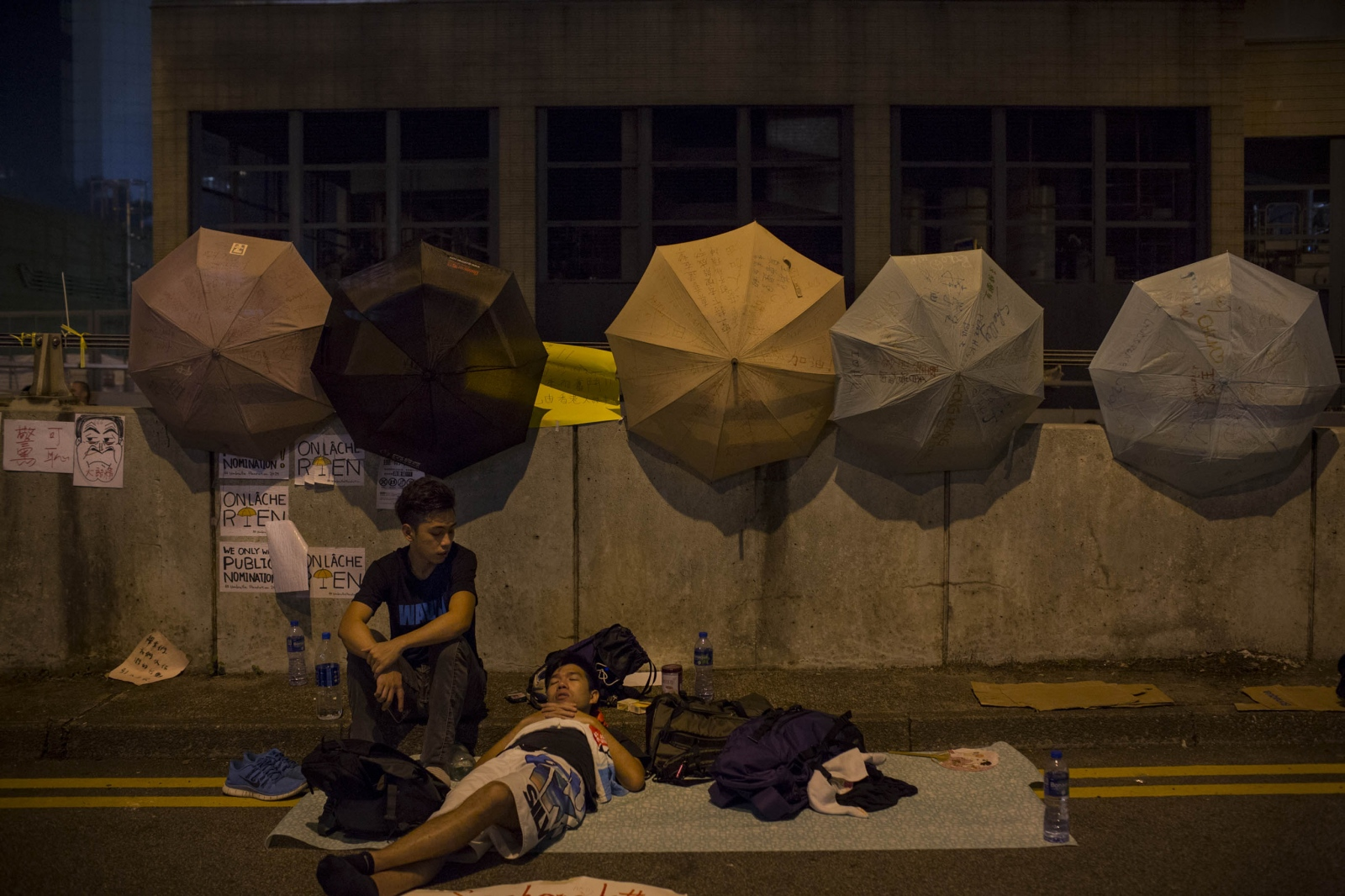 Protestors camp out in the roads of Admiralty district of Hong Kong, in the early hours of October 5, 2014, with umbrellas and pro-democracy posters written in various languages behind them.