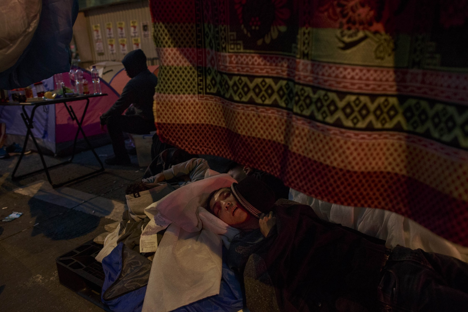 A protestor sleeps in a makeshift tent in the Mong Kok district of Hong Kong, on November 25, 2014. Pro-democracy demonstrators blocked and camped on major thoroughfares and roads of the city for just over two months, calling for universal suffrage in 2017 with the right to elect the city's own chief executive-- without Beijing's pre-approval of candidates-- a demand that remains rejected by Beijing.