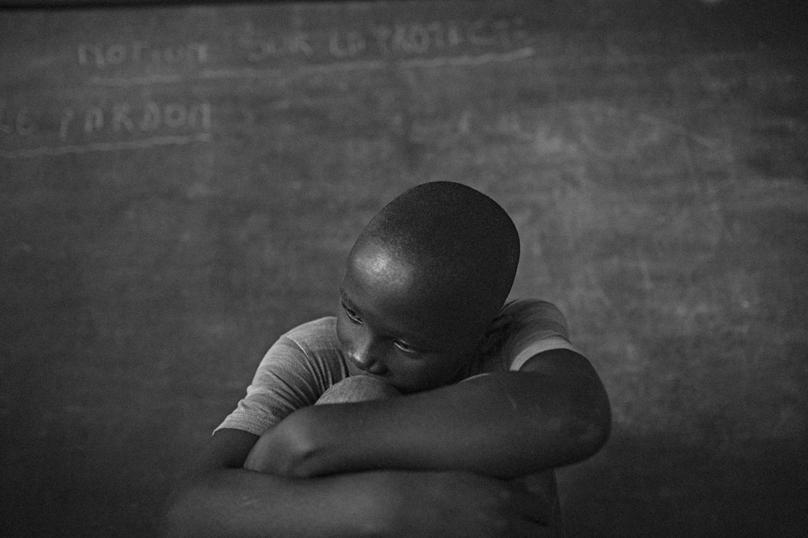 "Former FDLR child soldier Samuel, 15, sits in a makeshift classroom for a photo at UPDECO's reintegration center in Rutshuru, Eastern DRC, on Monday, July 21, 2014. Samuel spent two years in the Hutu-dominated militia group and left after realizing that it ""was not a good team,"" he said. He wishes to return to school and has fortunately reconnected with his family, but is currently staying with a transit family during the three-month reintegration period many child soldiers experience before returning home."