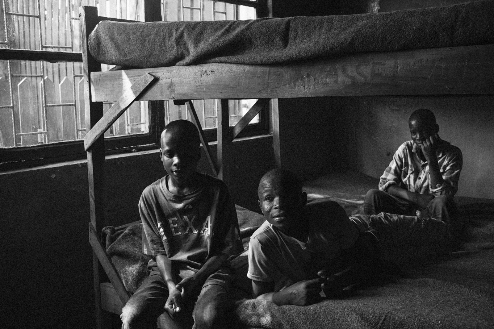 Paterne, 14, Josue, 14, and Yamankai, 16, sit on bunk beds in the BVES transit center in Bukavu, Eastern DRC, on Friday, July 25, 2014. All three are former child soldiers in various militia groups in the east of the country, and are currently awaiting reintegration.