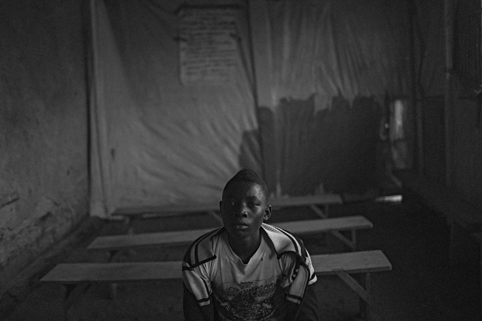 Former PARECO child soldier Habyarimana sits in a makeshift classroom in UPDECO's reintegration center in Rutshuru, Eastern DRC on Monday, July 21, 2014. Many child soldiers spend years in various militia groups in the east of the country, sometimes leaving them on their own accord, or after being convinced by elders or militia leaders to put down their weapons. The road to reintegration into society again is often a long one, especially if the child's family does not wish for them to return. Many of the boys and girls have missed out on years of schooling, and if they are older than 18, are not legally allowed to be in transit centers run by NGOs where they can receive some type of assistance in reintegration. Even so, many of these reintegration centers severely lack funding and therapists to help counsel the children, and they return home to the same conditions as before they joined the militia group.