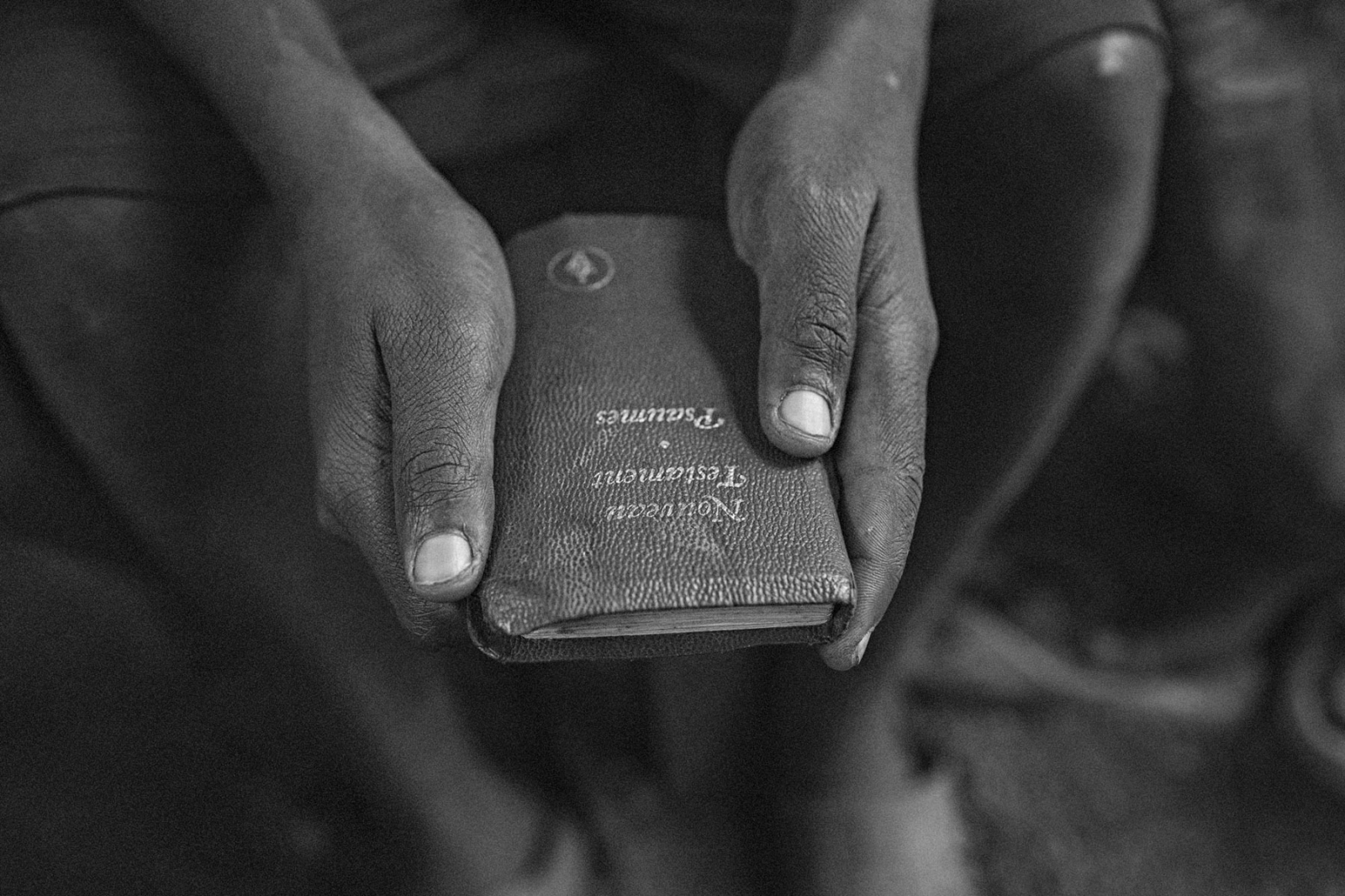 A former child soldier holds a book of Psalms in UPDECO's transit center in Rutshuru, Eastern DRC, on Monday, July 21, 2014.