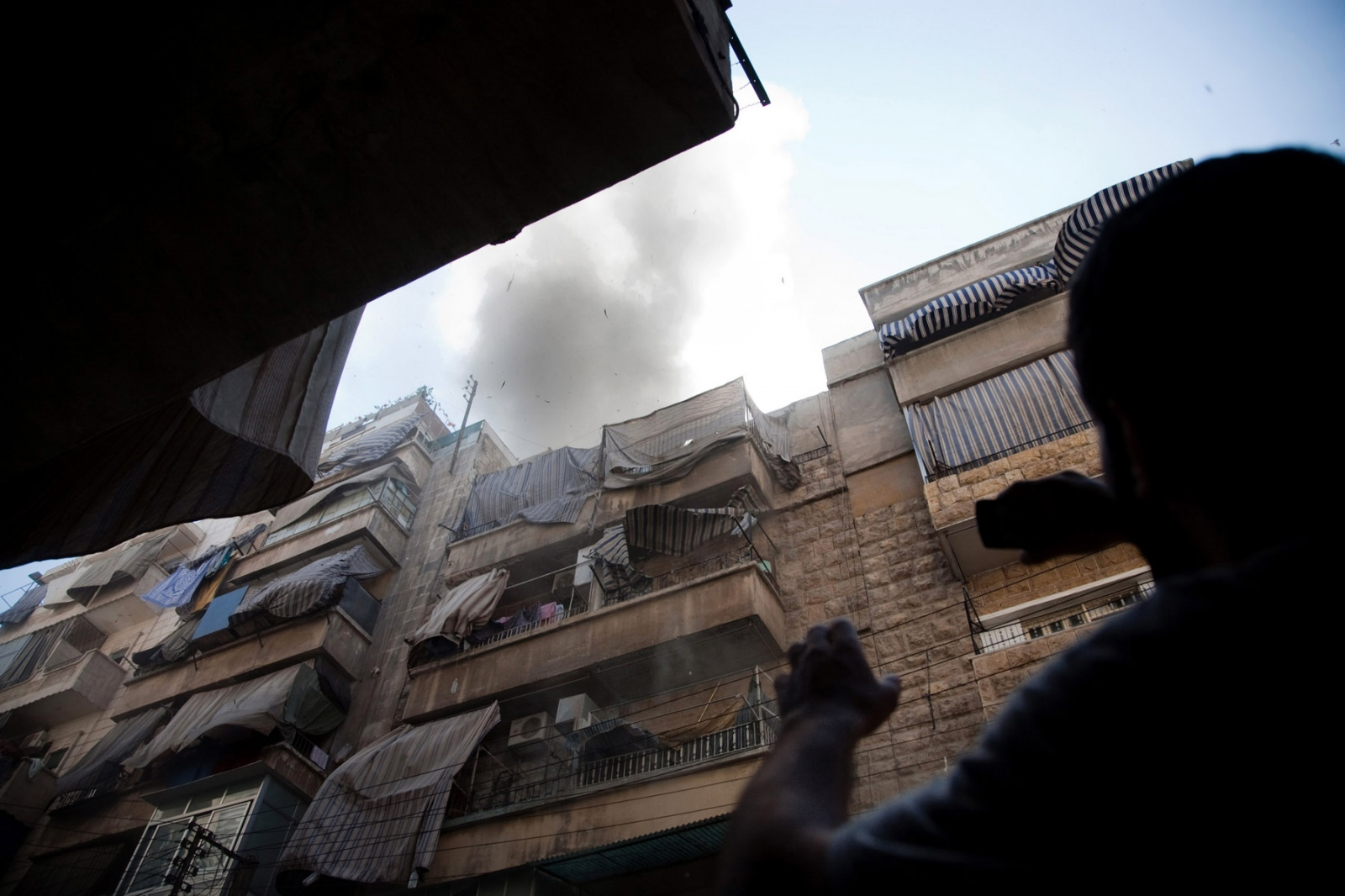A civilian films debris and smoke coming from an apartment building that was hit by an airstrike in the neighborhood of Bustan al Qasr in Aleppo, Syria, on Monday, August 6, 2012 which claimed at least eight lives including five children from the same family. At least two people, including a child, were trapped under rubble, complicating rescue attempts. Bustan al Qasr, a Free Syrian Army controlled district in south west Aleppo, has consistently been shelled and attacked by helicopters and planes over the last two weeks after the FSA entered Syria's commercial capital and its most populated city. According to the UN, over 200,000 civilians have fled the city, whilst many other displaced remain inside, seeking refuge in mosques, parks, and schools. Bustan al Qasr remains almost fully populated by its residents who chose not to flee.