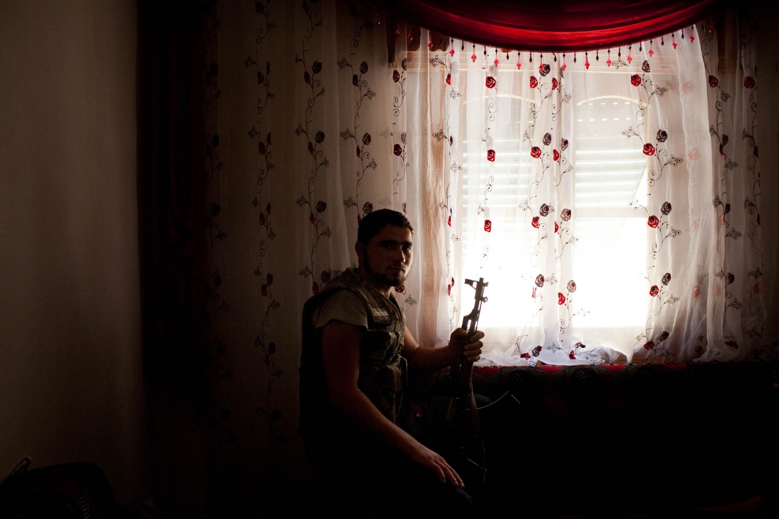 A fighter from the Free Syrian Army sits in an apartment on the lookout for Syrian Army tanks in the neighborhood of Salaheddin in Aleppo, Syria, on Tuesday, July 31, 2012. Fierce fighting erupted in Aleppo, Syria's commercial capital and its most populated city, one and a half weeks ago as FSA fighters poured in to the city with weapons to fight against the Syrian Army. Many of the battles have taken place in restive neighborhoods such as Salaheddin, which saw the biggest anti-government protests throughout the revolution. Almost all of the estimated 200,000 residents have fled to other areas of Aleppo for safety, and many men have stayed to fight alongside the FSA.