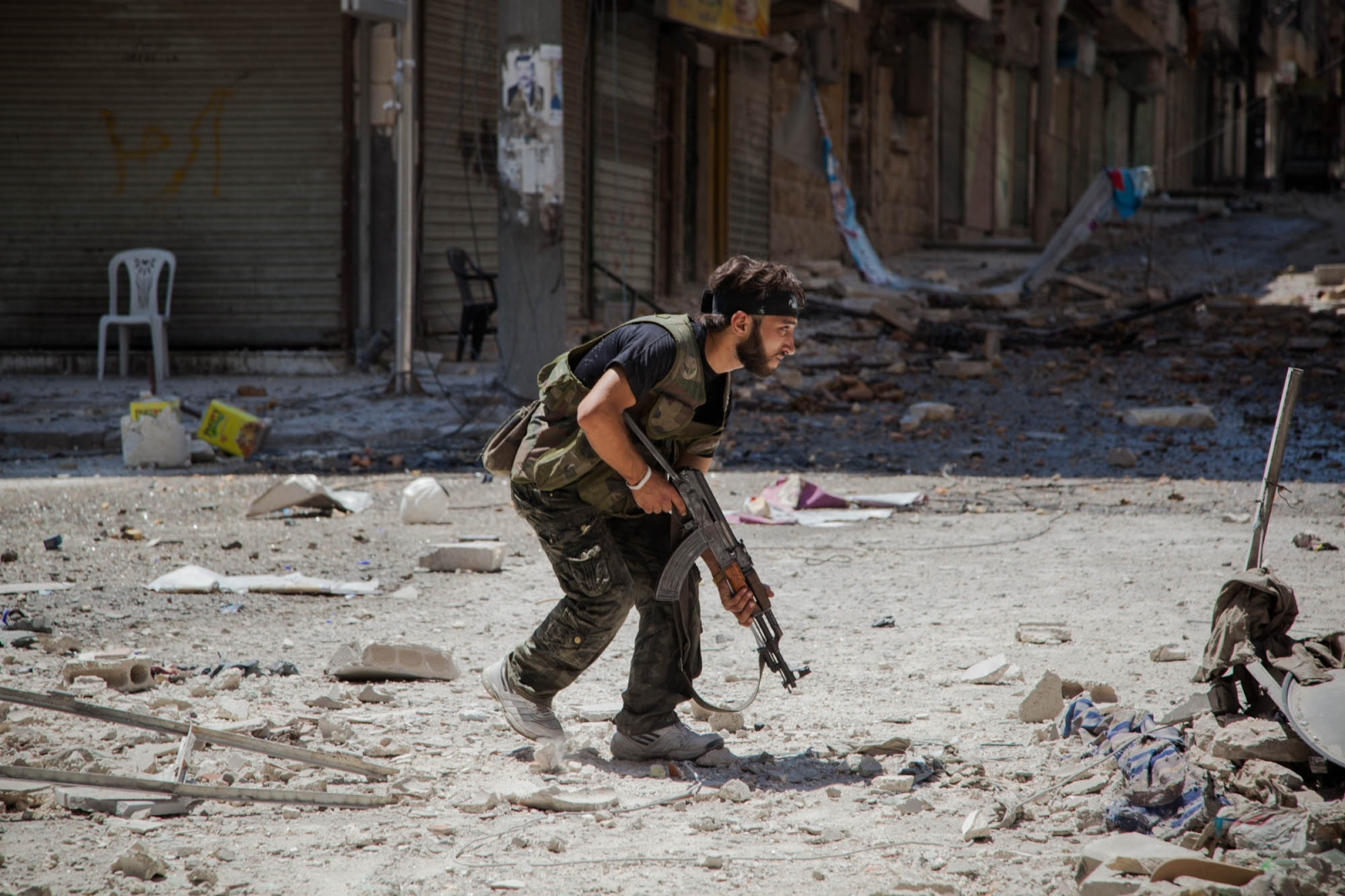A fighter with the Free Syrian Army runs out in to an intersection before firing at government forces on the frontline in the Salaheddine neighborhood of Aleppo, Syria, on August 8, 2012.