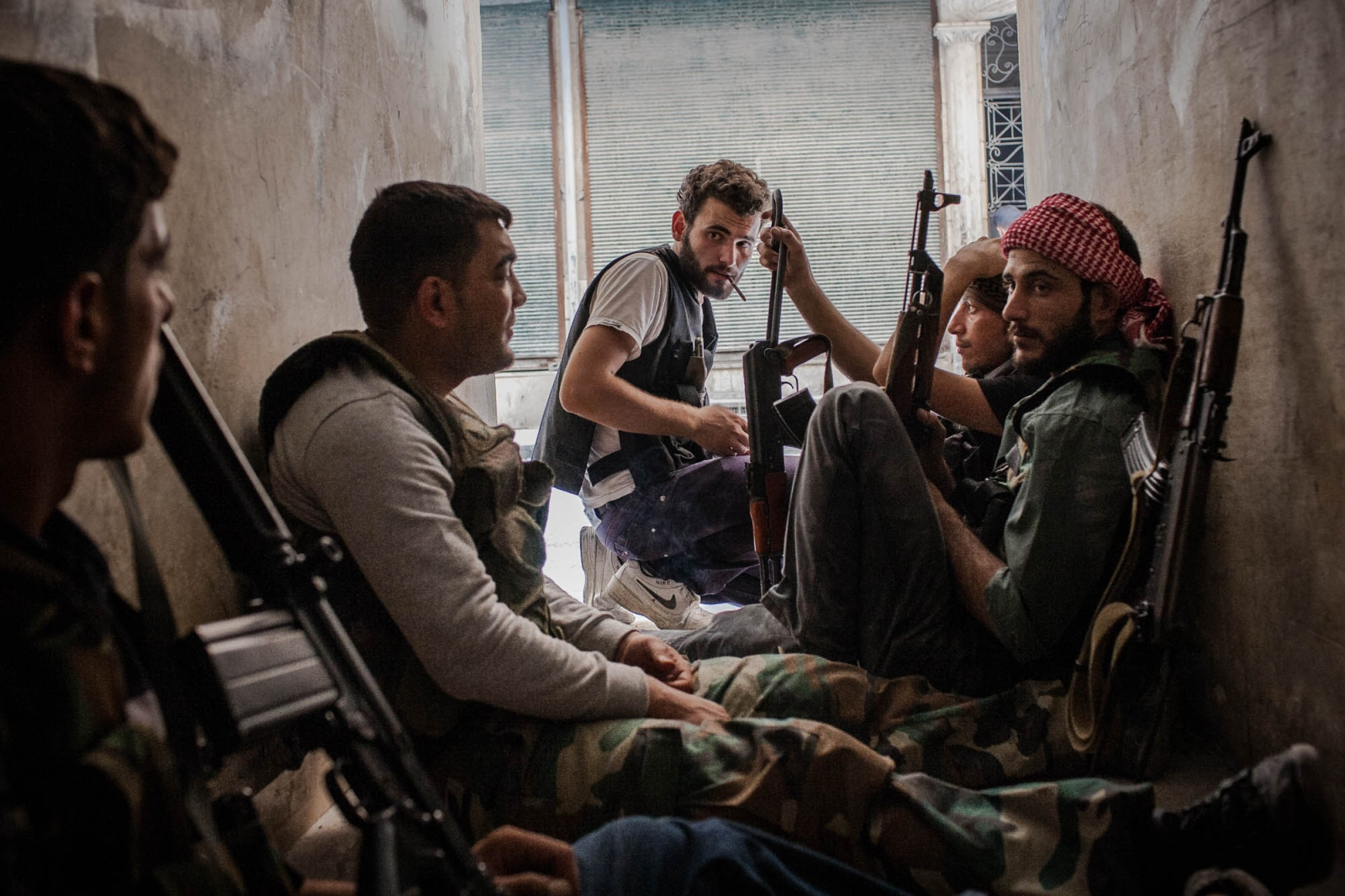 Fighters with the Free Syrian Army take cover from mortar shells in a hallway of a residential building on the frontline in the Salaheddine neighborhood of Aleppo, Syria, on August 8, 2012.