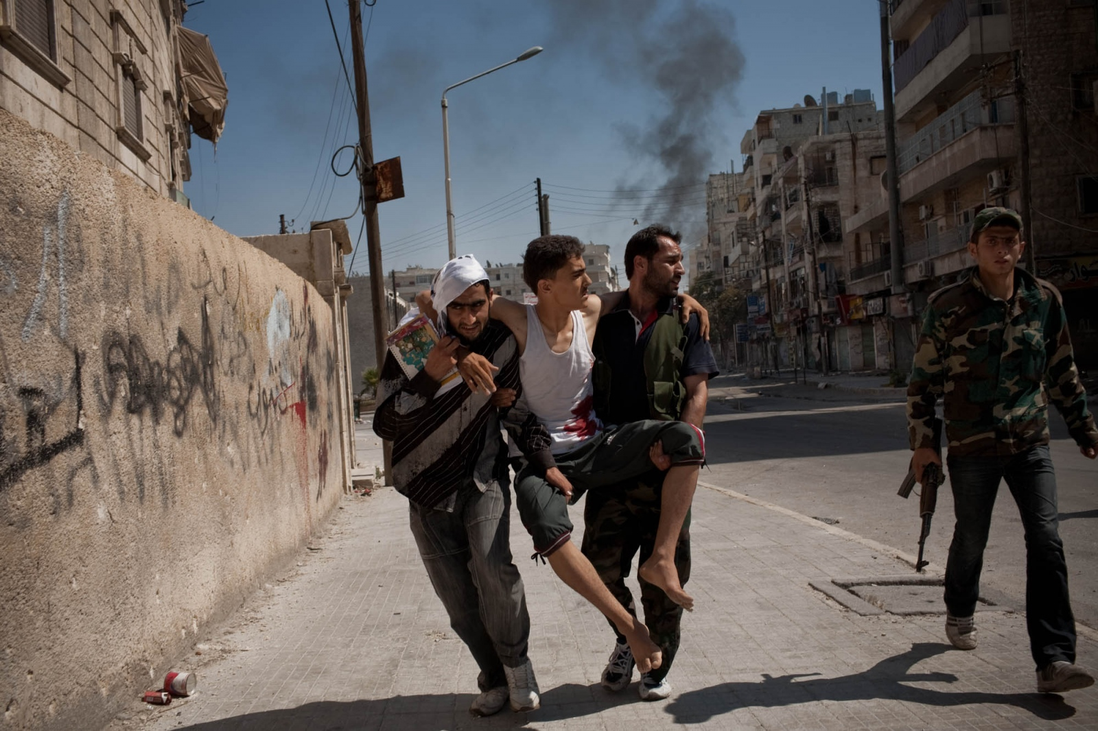Fighters with the Free Syrian Army carry an injured civilian to a field clinic following heavy shelling in the Salaheddine neighborhood of Aleppo, Syria, on August 3, 2012.
