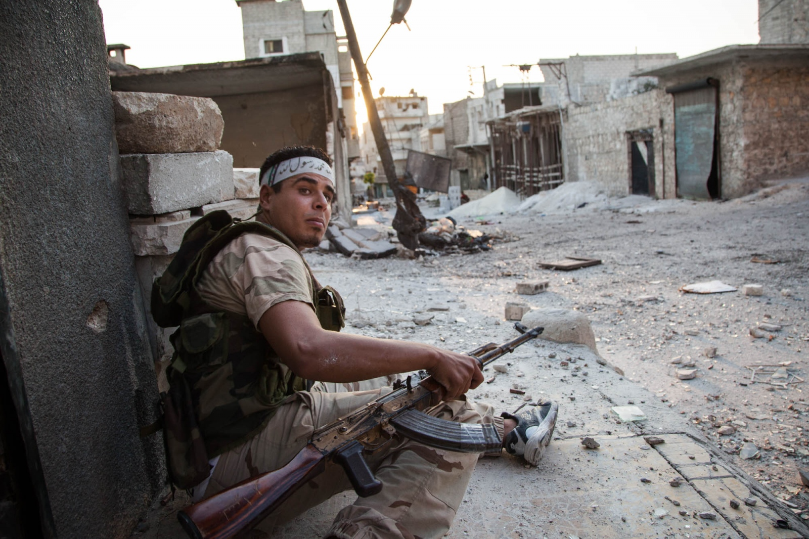 A fighter with the Free Syrian Army calls for assistance on a street corner where government snipers target the FSA, in the Salaheddine neighborhood of Aleppo, Syria, on August 28, 2012.