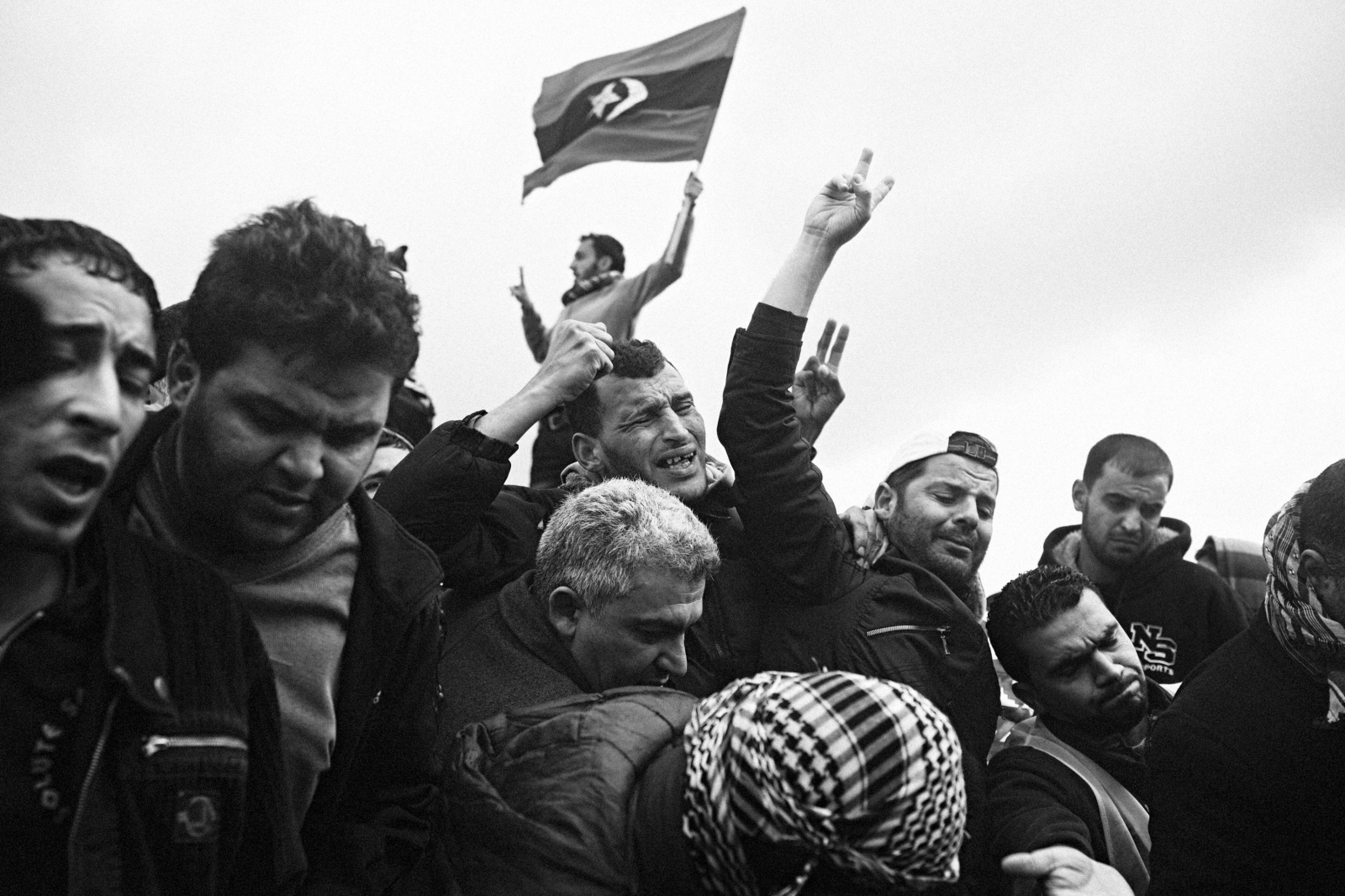 Men weep at the funeral of a friend who succumbed to his injuries sustained during the first days of the Libyan Revolution, in Benghazi, Libya on February 25, 2011.