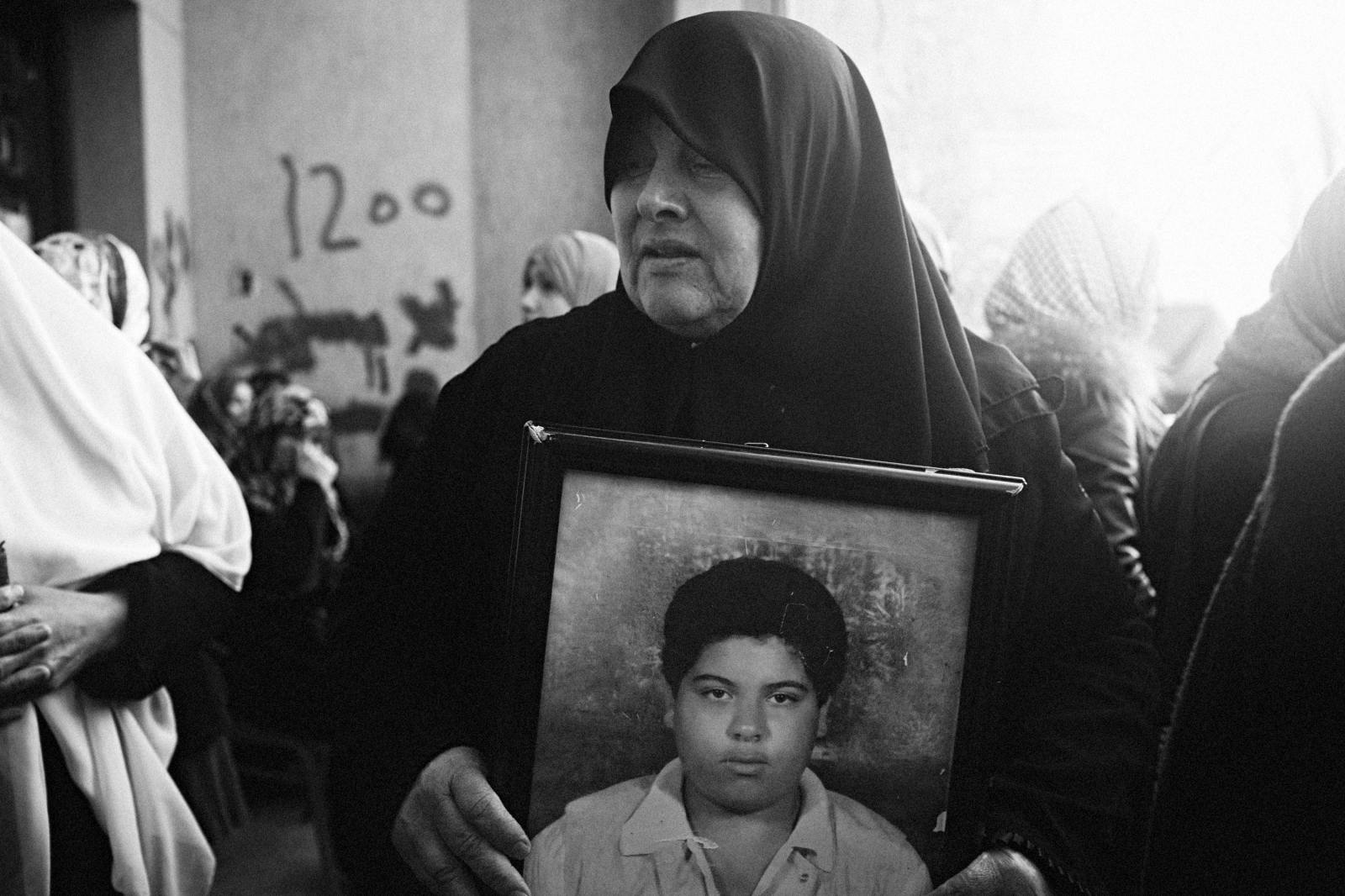 A woman holds a picture of her son, who she claims was killed in the 1996 Abu Salim massacre, along with over 1,200 other men. Benghazi, Libya, February 26, 2011.