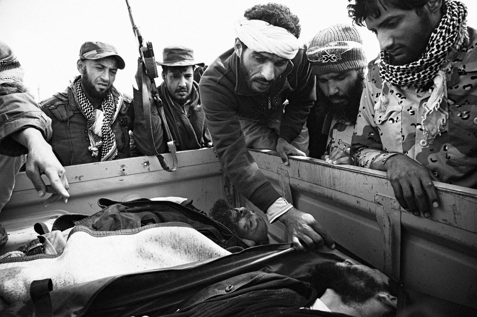 Rebel fighters attempt to identify their dead fellow fighters near the frontline between Ajdabiya and Marsa Brega on April 1, 2011.