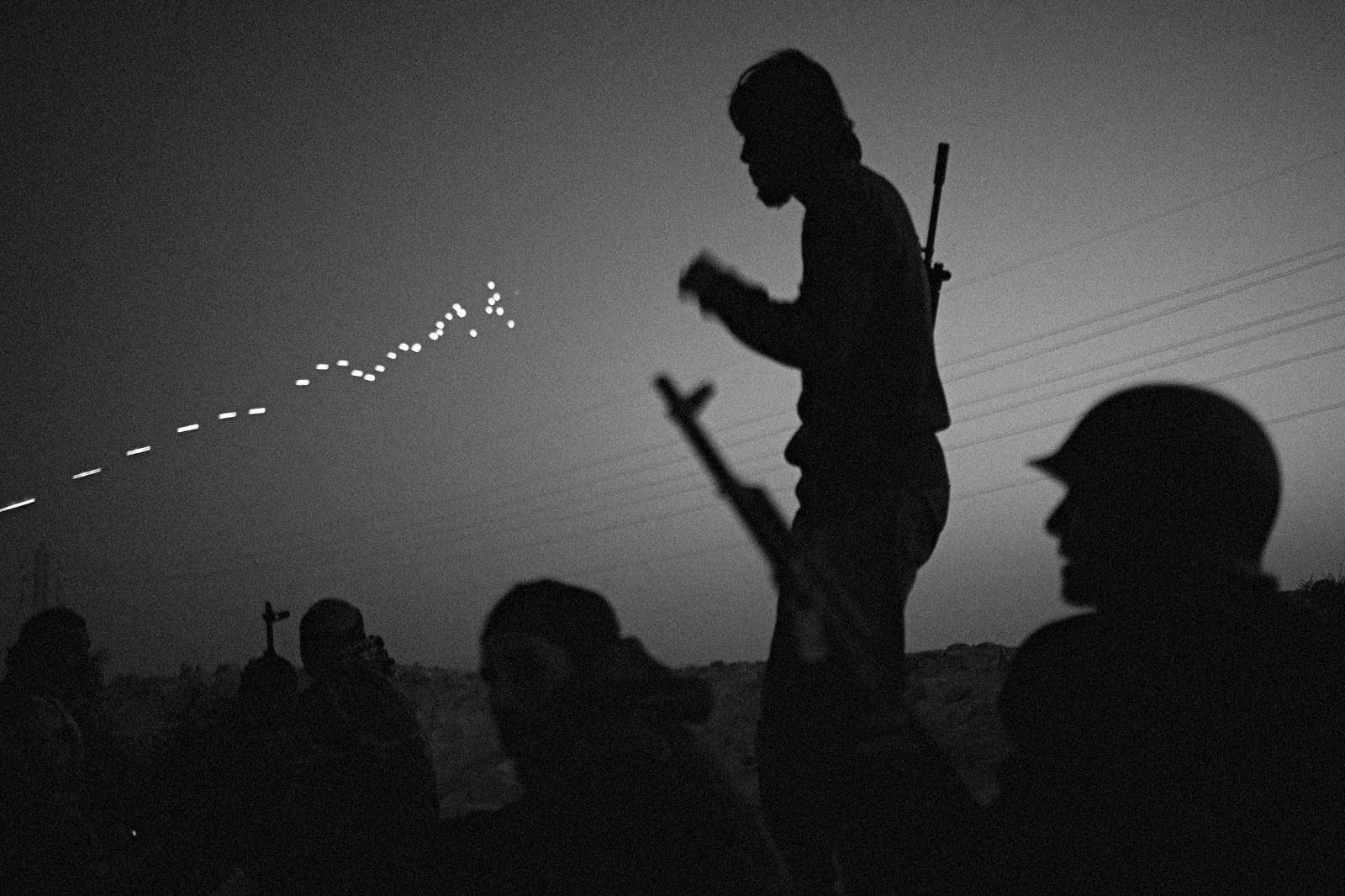 Rebel fighters at sunset on the outskirts of Ajdabiya watch tracer bullets light up the sky on March 25, 2011.