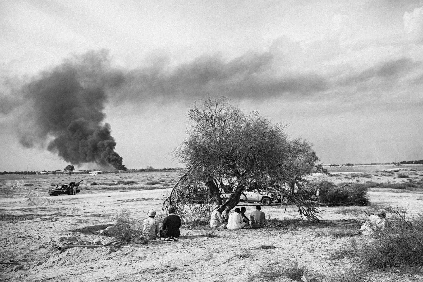 Farm buildings burn in the distance as fighters rest on the outskirts of Sirte, October 7, 2011.