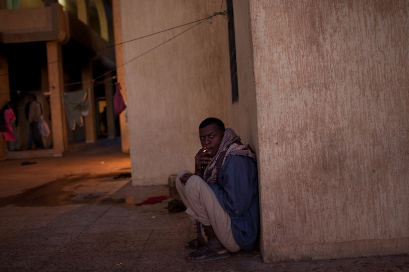 A migrant smokes a cigarette in a detention facility in Kufra, southern Libya on March 7, 2012.
